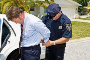 A police officer arrests and handcuffs a man.